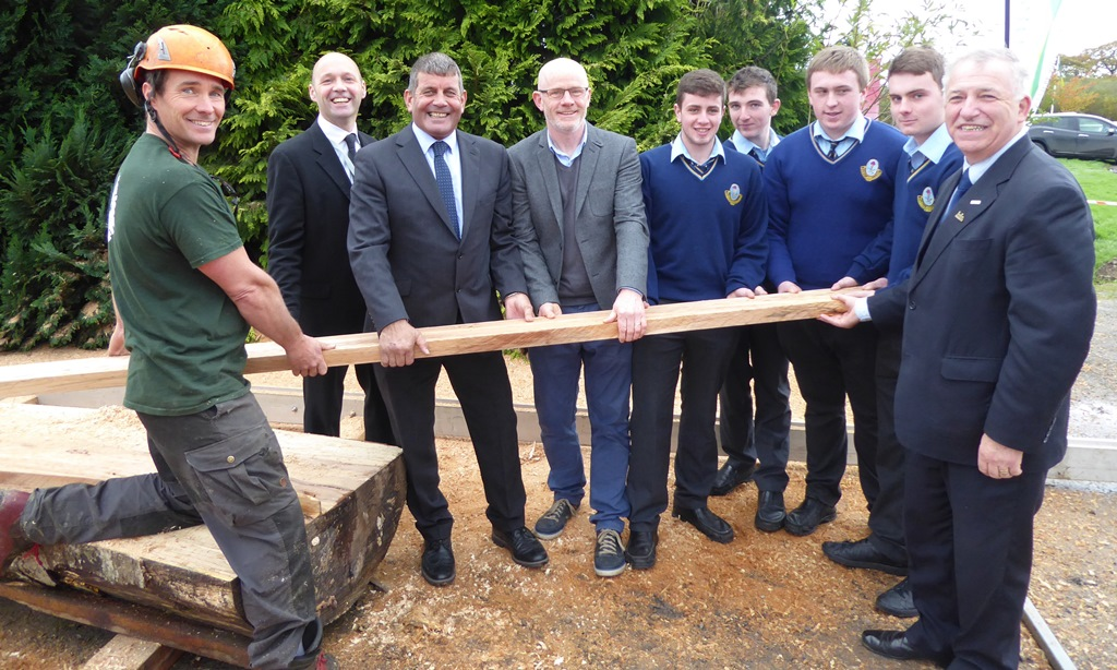 Eoin O'Connell of Arborist Tree Services with John Casey Forestry Adviser with Teagasc, Minister of State Andrew Doyle TD and Professor Gerry Boyle, Teagasc Director present a freshly sawn beech plank to teacher Paddy Crowley and woodwork students of Coláiste an Chraoibhín, Fermoy, Co Cork.